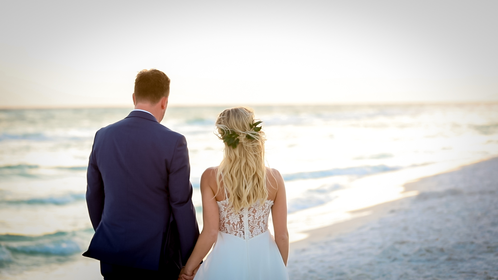 Bride and groom walking on the beach in Seaside, Florida at sunset